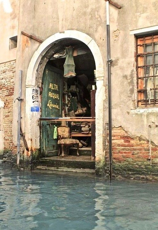 "Libreria, Venezia. Via VS. ""High Water Library"" painted on the door in Italian."