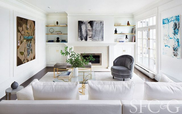 A neutral living room with a fireplace, a gray velvet sofa, and a white sofa