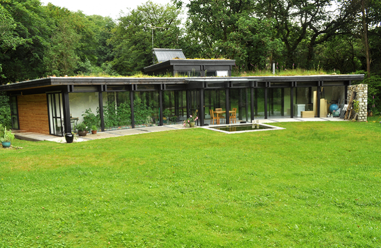 The single storey house is topped with a green roof for Building a cottage on a budget