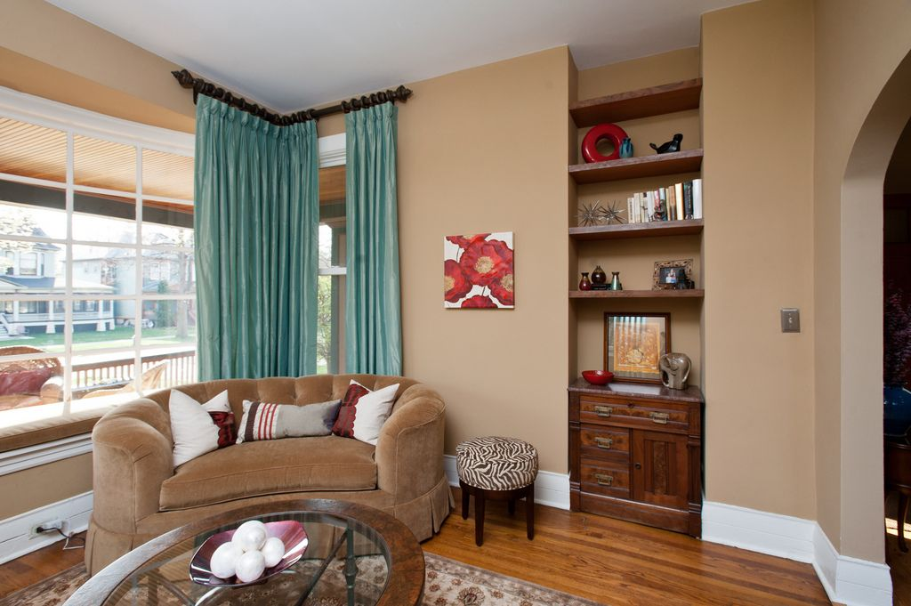 Living or seating room light teal draperies neutral beige walls white trim red and purple for Beige and purple living room