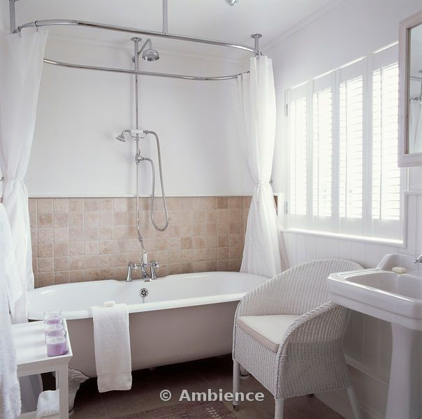 Bath Shower Rail white curtains on oval shower rail above white clawfoot bath in