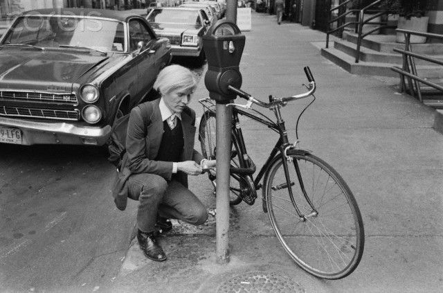 Andy Warhol Locking His Bike --  Photograph by Robert Levin, 1981.  Andy Warhol locks bicycle to parking meter, E. 11th Street.