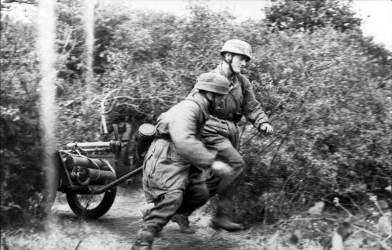 Two German Fallschirmjäger (paratroopers) pull a handcart loaded with equipment while running through the brush following the Allied Invasion of Normandy. Near Bayeux, Calvados, Lower Normandy, France. 21 June 1944. Image taken by Toni Schneiders.