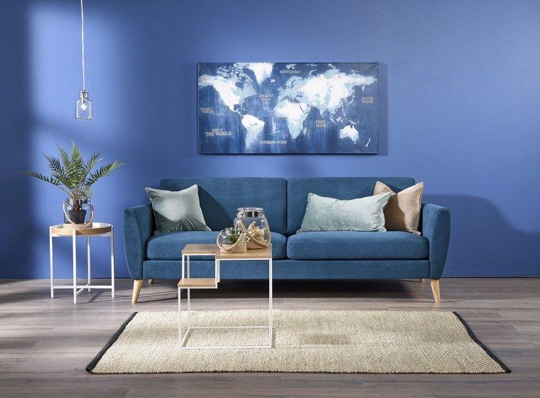 salotto con pareti di colore blu e un divano di velluto