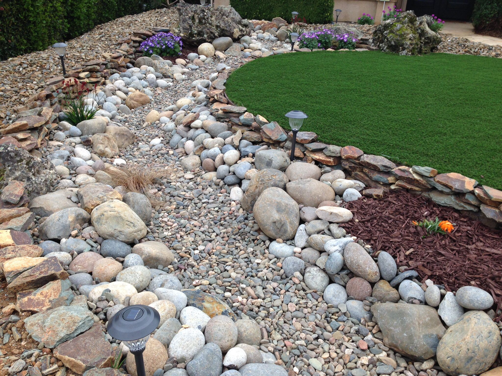 new front yard dry creek bed artificial turf basalt fountain