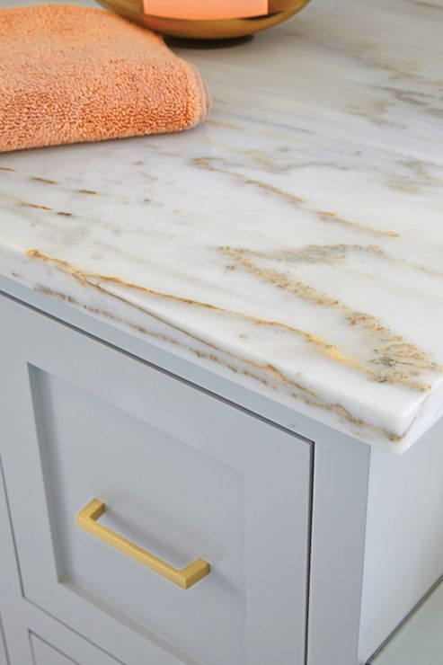 Stunning bathroom vanity painted light grey accented with unlacquered brass hardware and topped with white marble with gold and bronze veining.