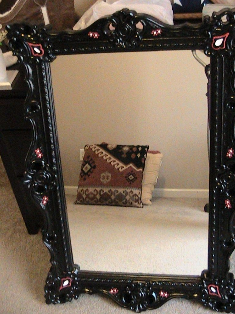 This is an old mirror that Rhiannon spray painted black and added red and white paint to accent.
