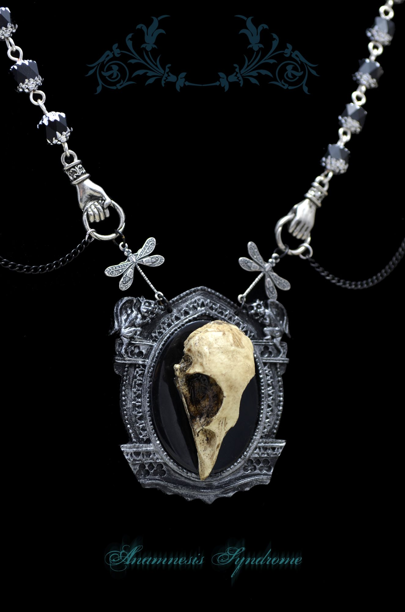 What you see is what you get.  A necklace in black and silver, with a fake bird skull (resin) onto a gothic setting with little gargoyle. Black chain, cathedral glass beads (black and silver), dragonflies and hands. Ends with a lobster clasps. One size fits all (thanks to the extended chain)....