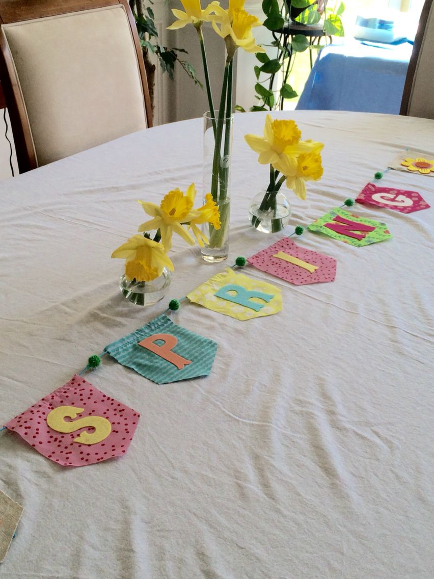 Easy Easter/Spring decor! Flowers in vases, lay banner on table rather than hanging.