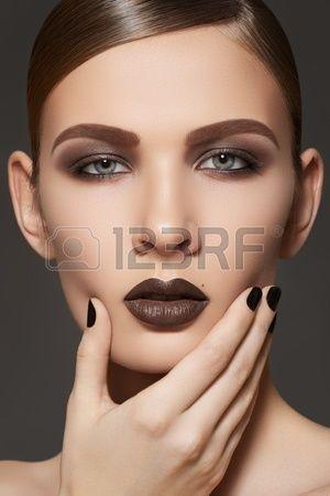 Fashion, manicure, kosmetyki i makijażu. Ciemny makijaż usta i paznokcie polski. Close-up portret modelki z brązowej szminki, paznokcie i skórę czystą czarnych. Shiny zaczesane do tyłu fryzury