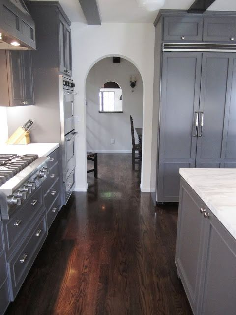 Arched entry way out of a kitchen with dark grey cabinets and drawe ...