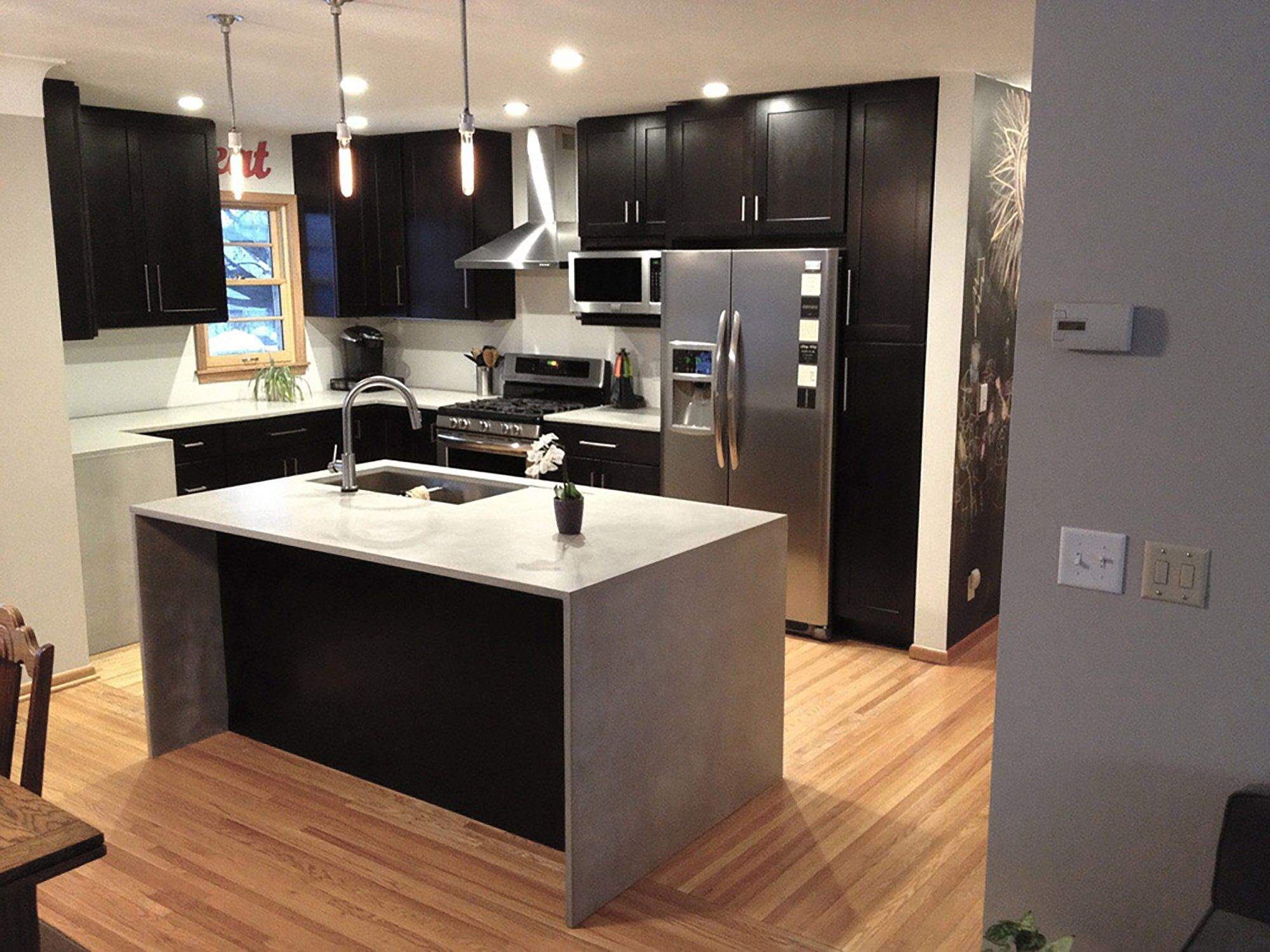Contemporary Kitchen Design Uses Black Shaker Cabinets And Waterfall Style  Counter On Island