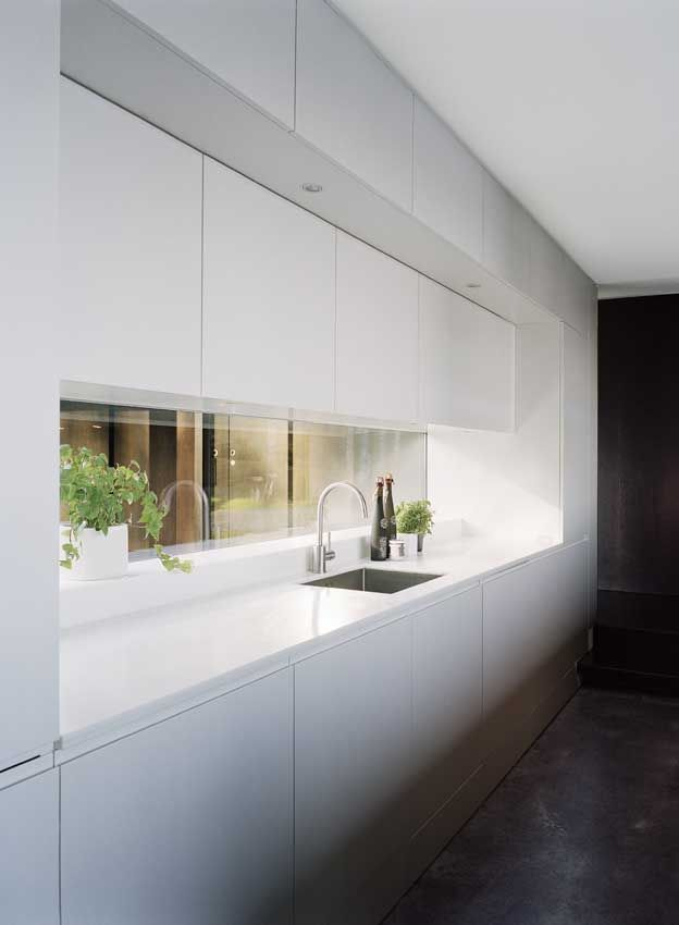 back wall of kitchen - reflective surface, lacquered cabinetry above.