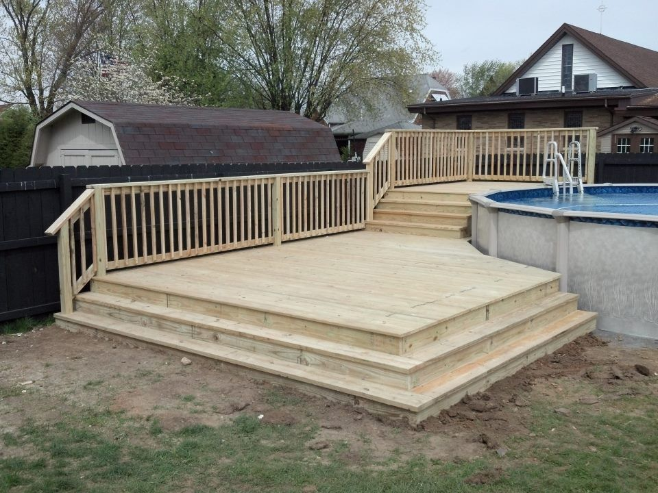 this is a custom two tiered deck with wrap around stairs built around an above ground pool - Above Ground Pool Deck Off House