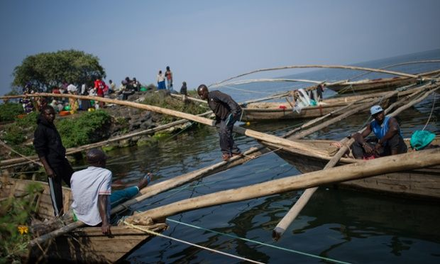 A fisherman walks between traditional wooden boats on the shore of Lake Kivu in Goma, Democratic Republic of the Congo. Photograph: Phil Moore/AFP/Getty Images
