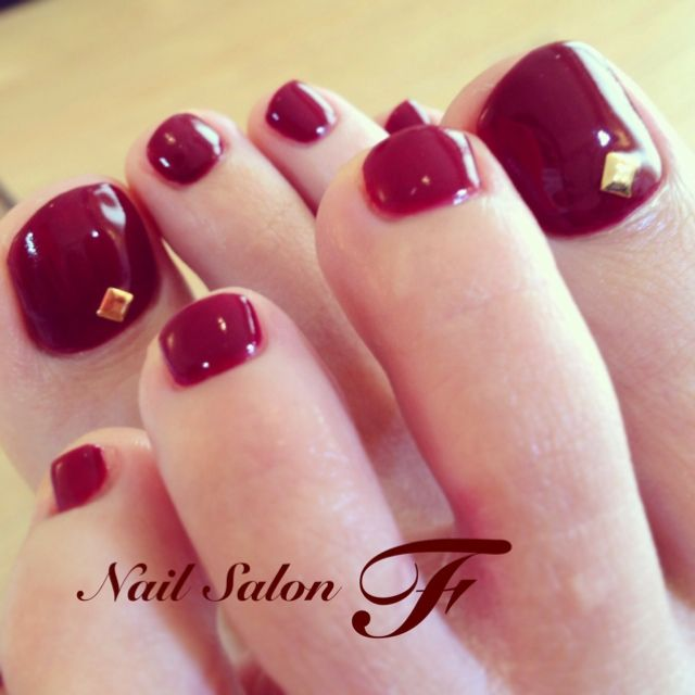 red pedicure with gold square charm