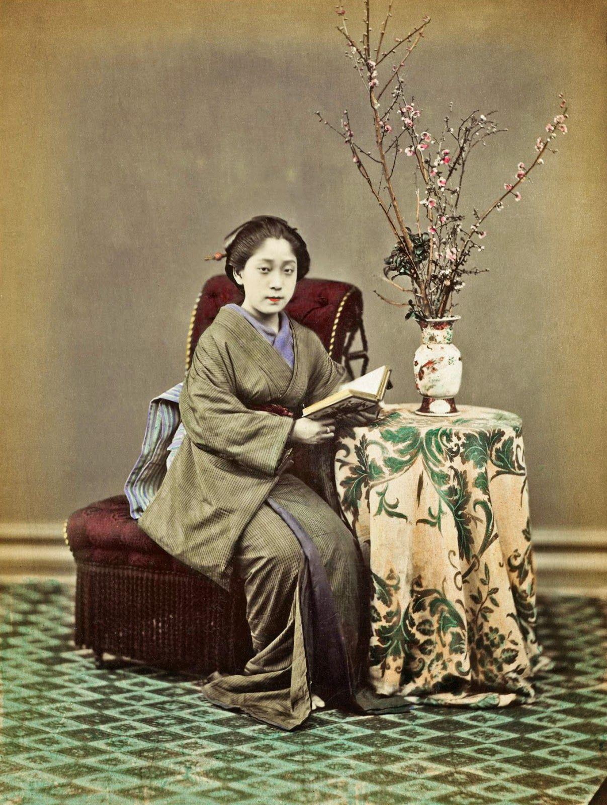 Woman reading a book near a vase with the sakura ikebana