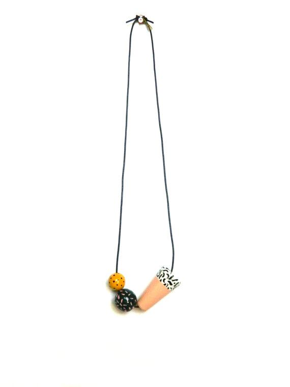 Allowing juxtaposing patterns and colors to create the rhythm. 3 wooden beads all varying in size are strung on an adjustable, black, leather cord and