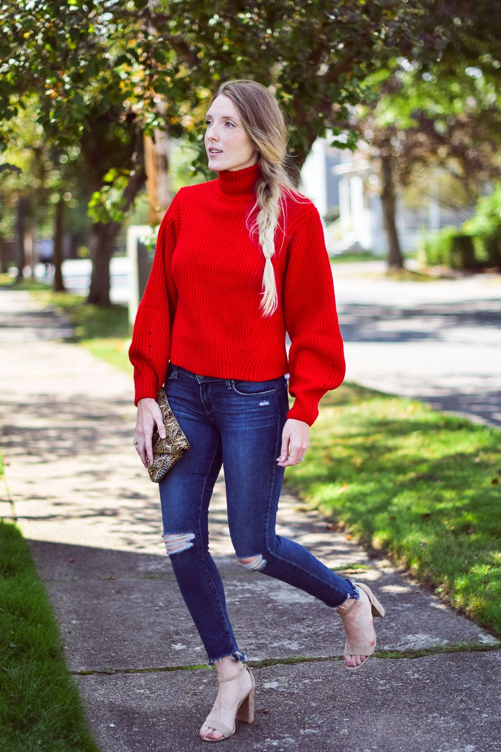 c08c65550461 Leslie Musser wearing a bright chunky red sweater with step hem jeans and  block heel sandals