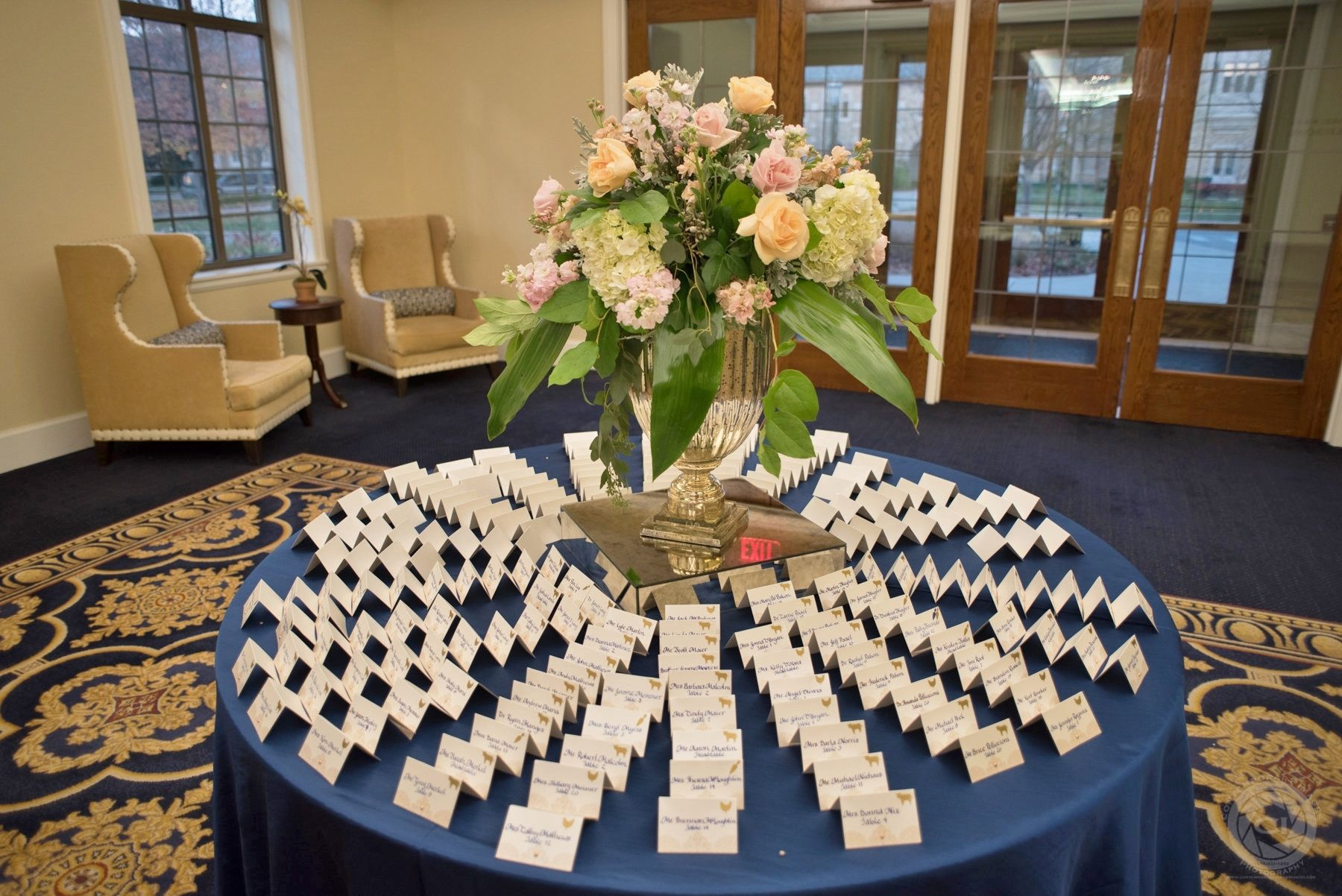 Beautiful place card display around tall floral centerpiece. Navy blue calligraphy was done by hand on each of the ivory escort cards. I loved the gold meal selection stickers on each card. They were perfect for our navy and gold wedding at the University of Notre Dame.