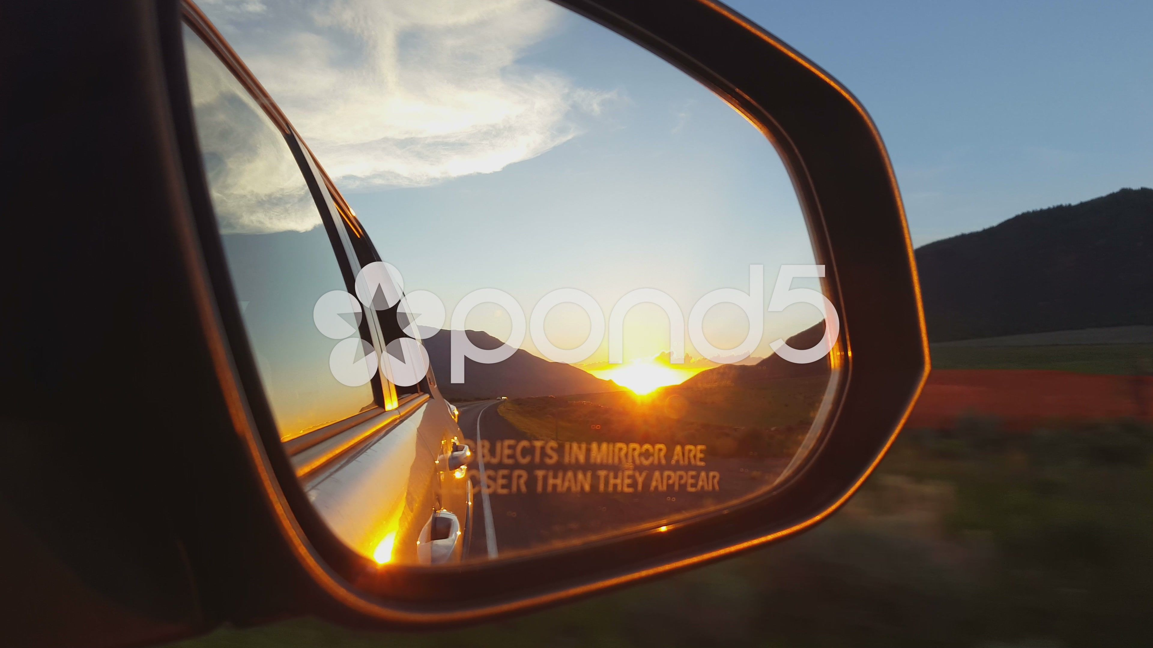 POV - Briliant sunset in mountain pass in auto rearview