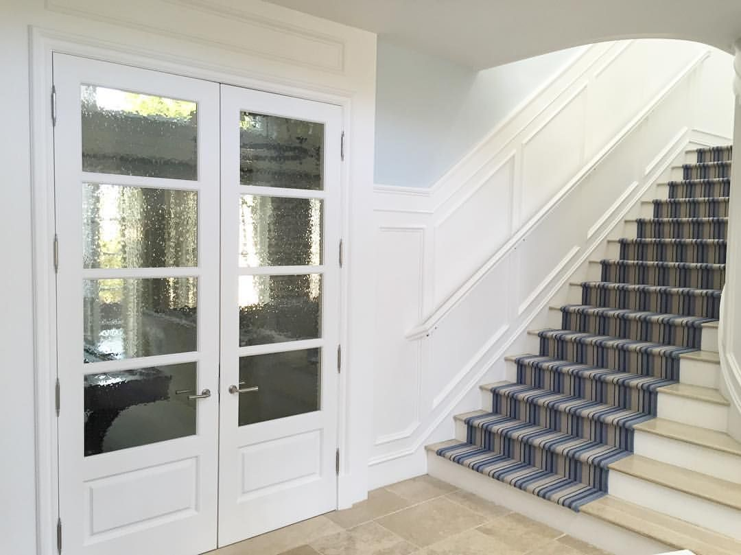 Seeded glass french doors |  white millwork | grand entrance #bwd #entry #stairrunner #frenchdoors #seededglass #interiordesign #customhome #coastaltransitional