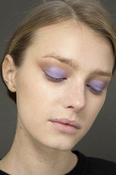 Lilac shadow in the centre of the lids with a taupe shade used under and around the eyes for a feline shape with flawless skin and strong brows and natural lips completed the look at Chole Fall/Winter 2014-15