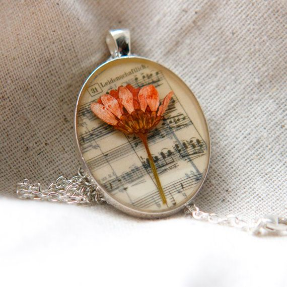 Resin jewelry pressed flower necklace. A pretty peach colored daisy mum flower was used for this musical pendant! A sheet music note backing add whimsy and charm to the necklace. This pendant was set in a clear glossy resin. A very romantic and nostalgic, unique necklace!    This is a completely one of a kind, unique necklace sure to start conversations. All of my jewelry comes packaged ready for gift giving and with a care sheet.      Large or small Pendant: Large  Necklace setting: silver…