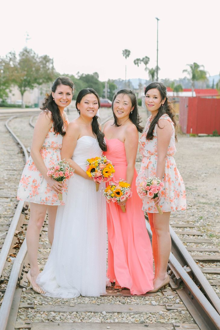 The maid of honor is wearing a strapless coral floorlength dress