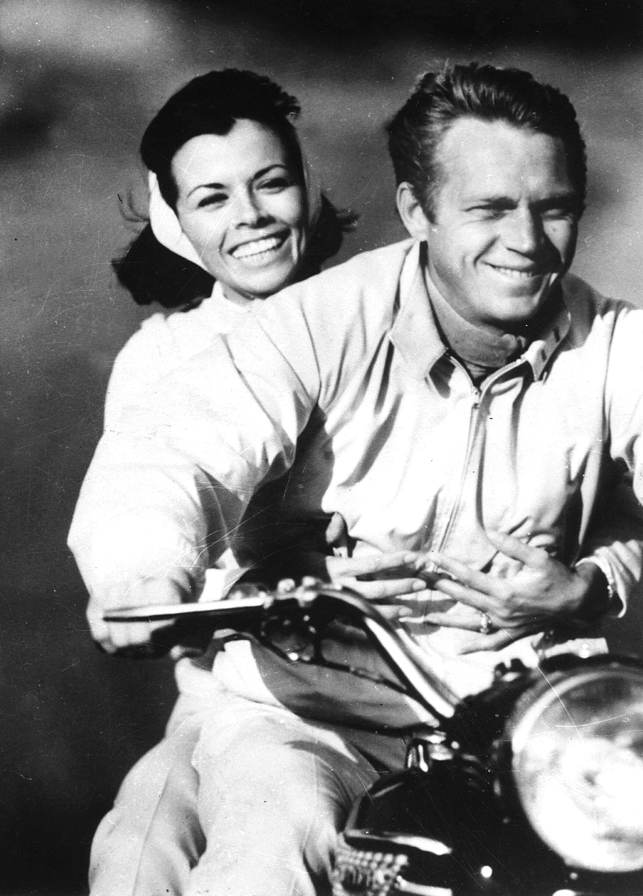 1966. Virée à moto pour l'acteur Américain Steve McQueen et son épouse Neile Adams . Passionné de moto, il disputera de nombreuses courses dans les années 60 avant d'être sélectionné par la fédération américaine pour faire partie du Team USA au championnat du monde d'enduro. Photo : archives Paris Match