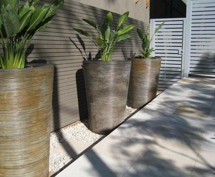 Sandstein Terrassenfliesen, große Pflanzkübel und weißer Zierkies ...