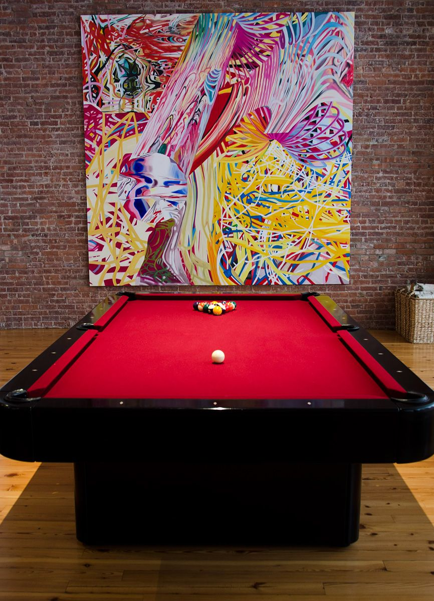Here is a black billiard table with red cloth. It is located in an ...