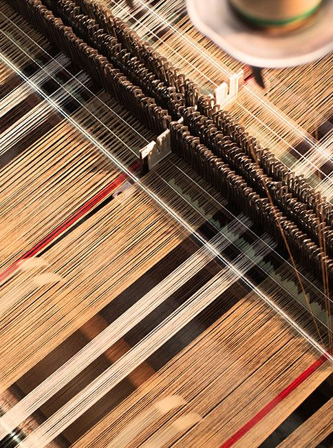 Camel, red, ivory and black – the iconic colours of the Burberry heritage scarf come together on the loom