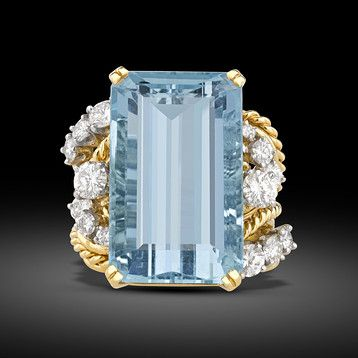 A stunning, pastel blue emerald-cut aquamarine weighing a dazzling 23.30 carats glistens in this eye-catching ring. Displaying a magnificent Mediterranean-blue hue, the stone is stylishly presented in an 18k yellow gold setting with sparkling white diamonds totaling 1.50 carats.