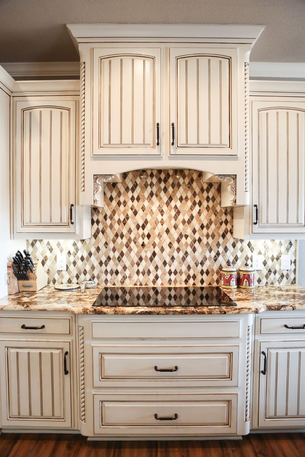Detail of antique white kitchen cabinets with harlequin diamond