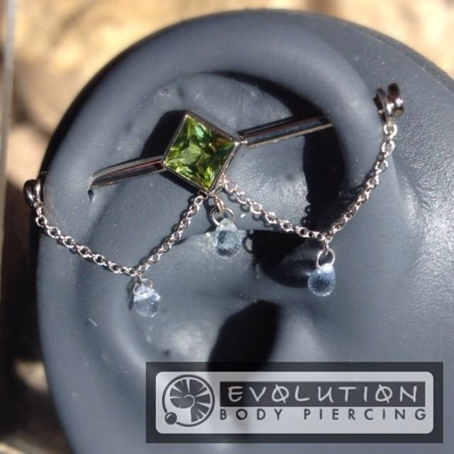 First of its kind! Genuine #peridot set in #whitegold with #platinum chain and white #sapphire #brilloletes designed to accommodate virtually any standard #industrialpiercing Jewelry built by #bvla...