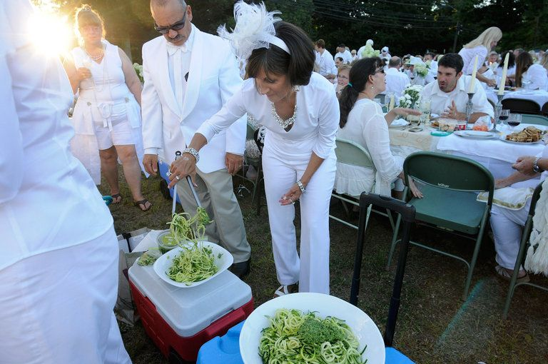 Joanne Raia, of Tolland, a raw food chef, tosses zucchini pasta with basil pumpkin pesto with sun-dried tomatoes and kalamata olives for her group of friends attending An Evening in White, a fundraiser for the United Churches of Durham, on Main Street in Durham Sunday.