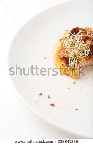 tasty handmade vegeterian pizza leftover in a white dinner plate - stock photo