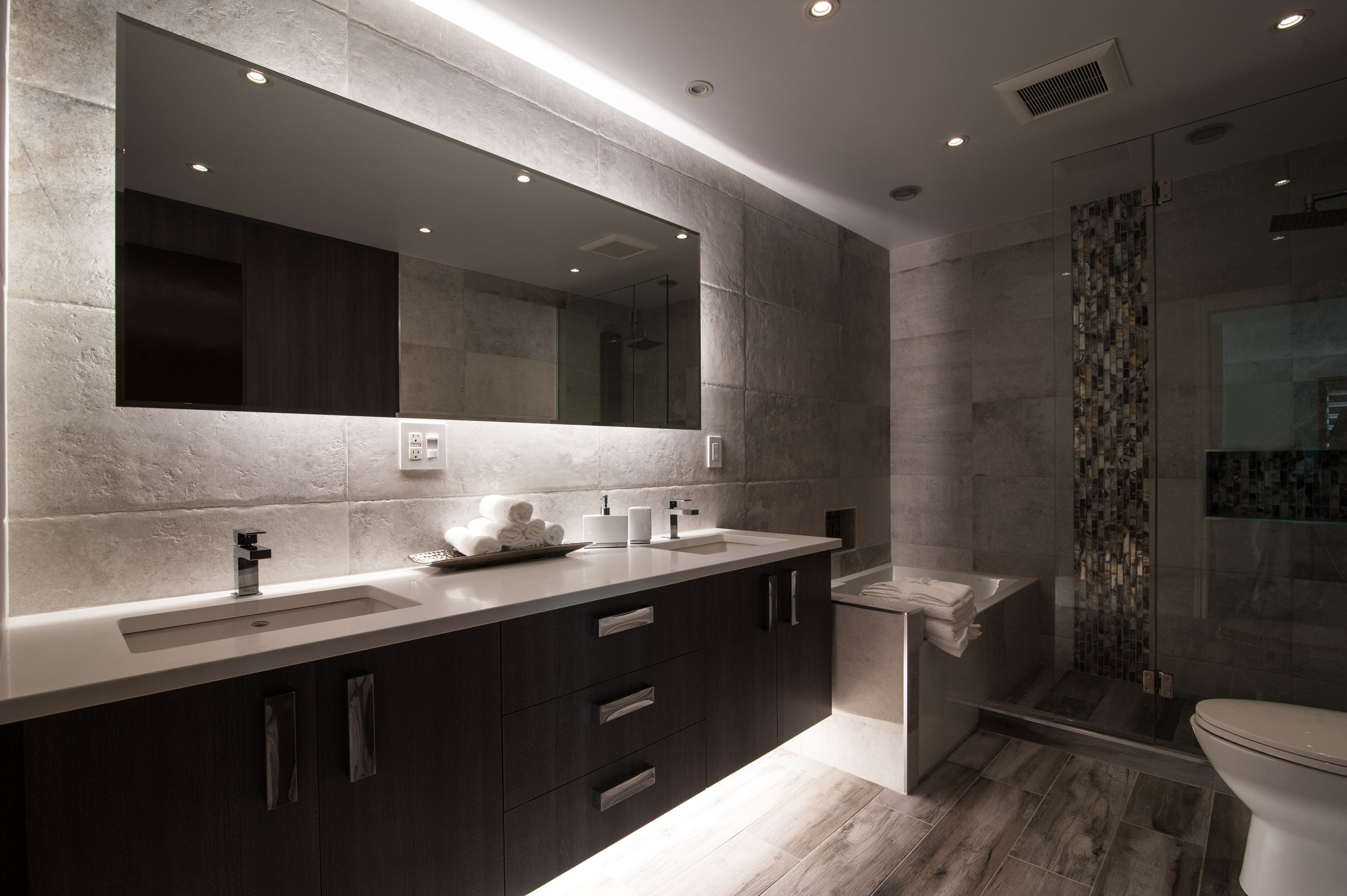 Large rectangular wall mirror in bathroom with glowing ...