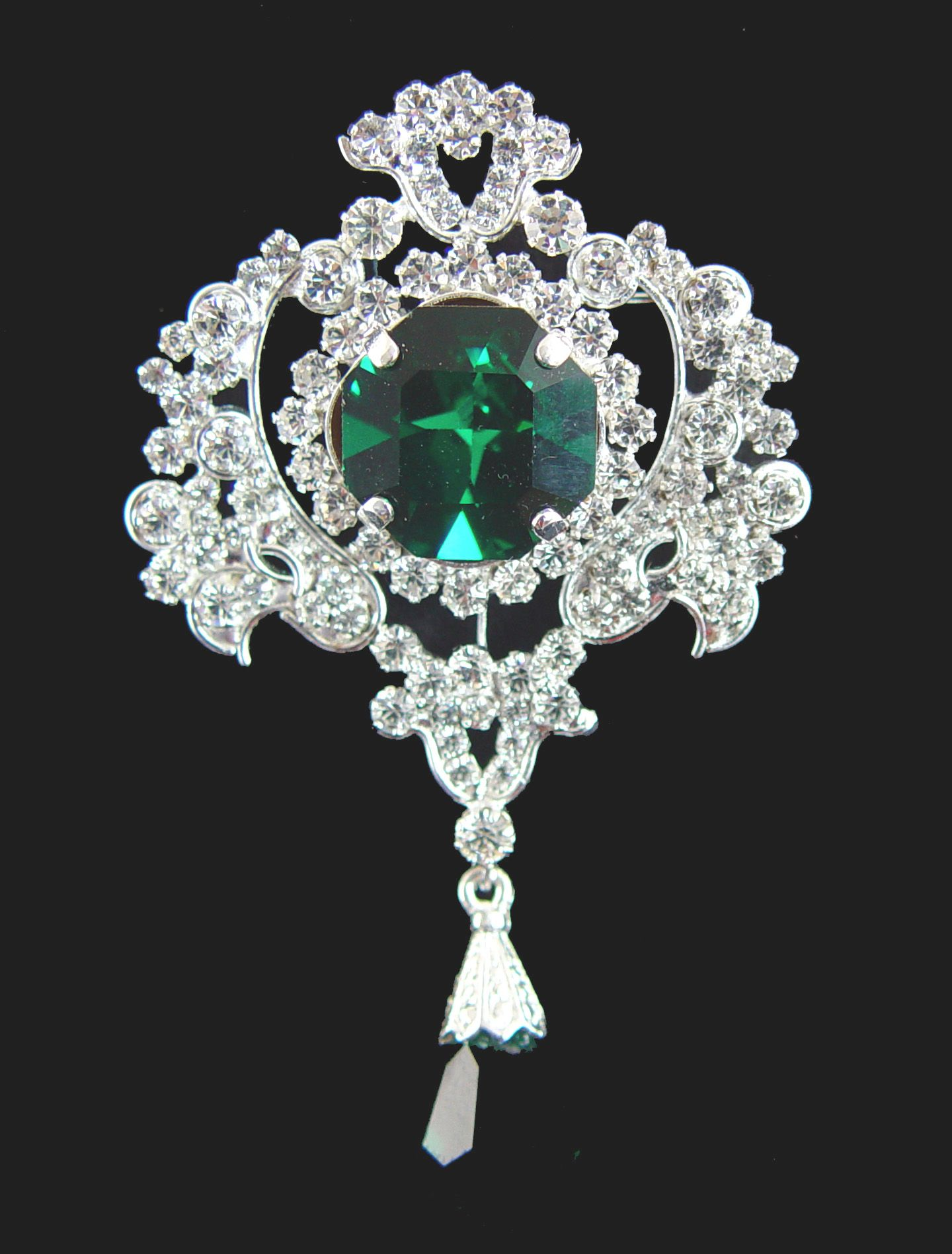 The diamond scroll brooch with the centre lozenge shaped emerald was made by taking the centre of the Stomacher and hanging the emerald drop from the Cullinan VIII