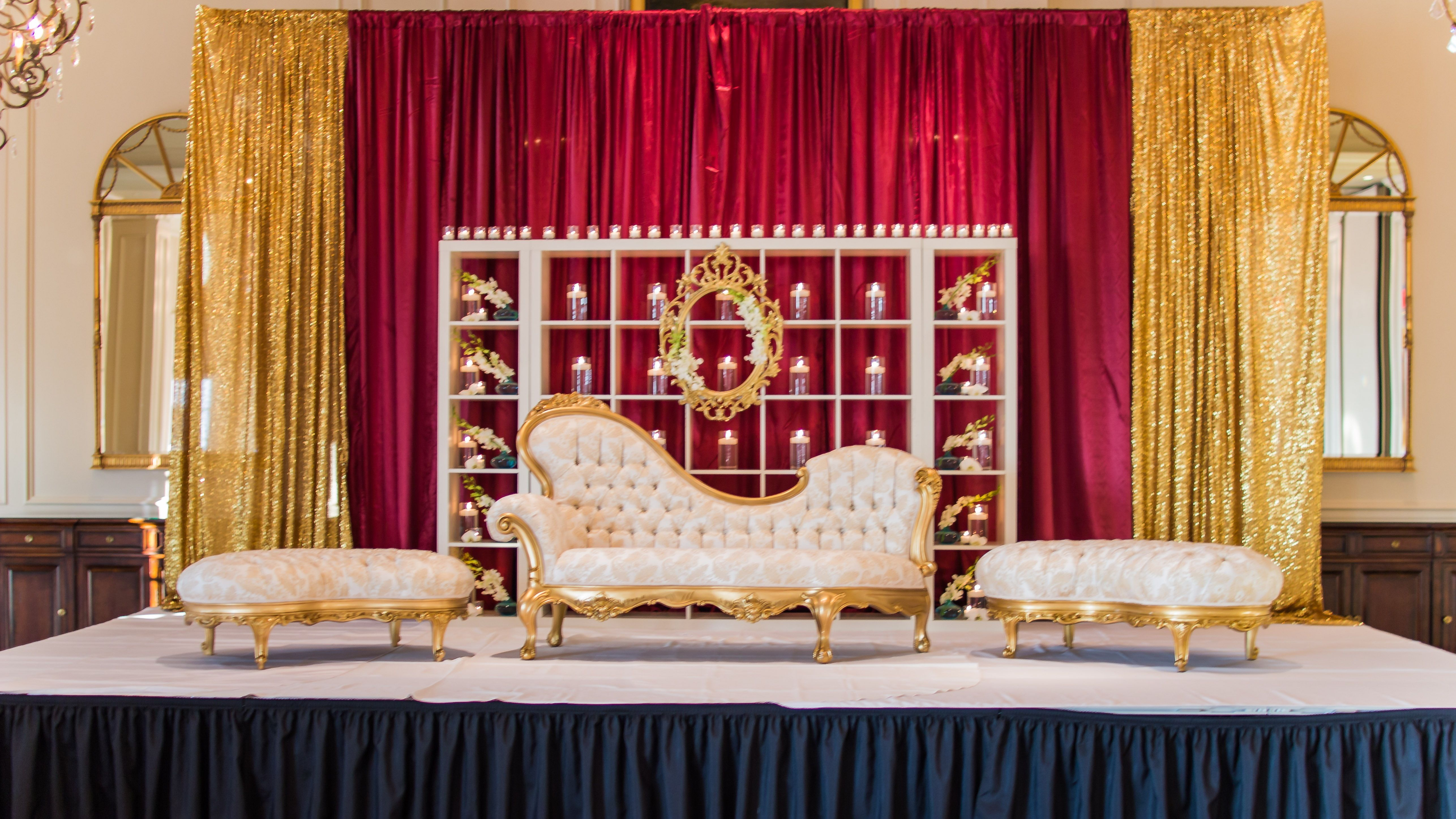 Red and gold draped wedding reception stage with candles for 25th wedding anniversary stage decoration