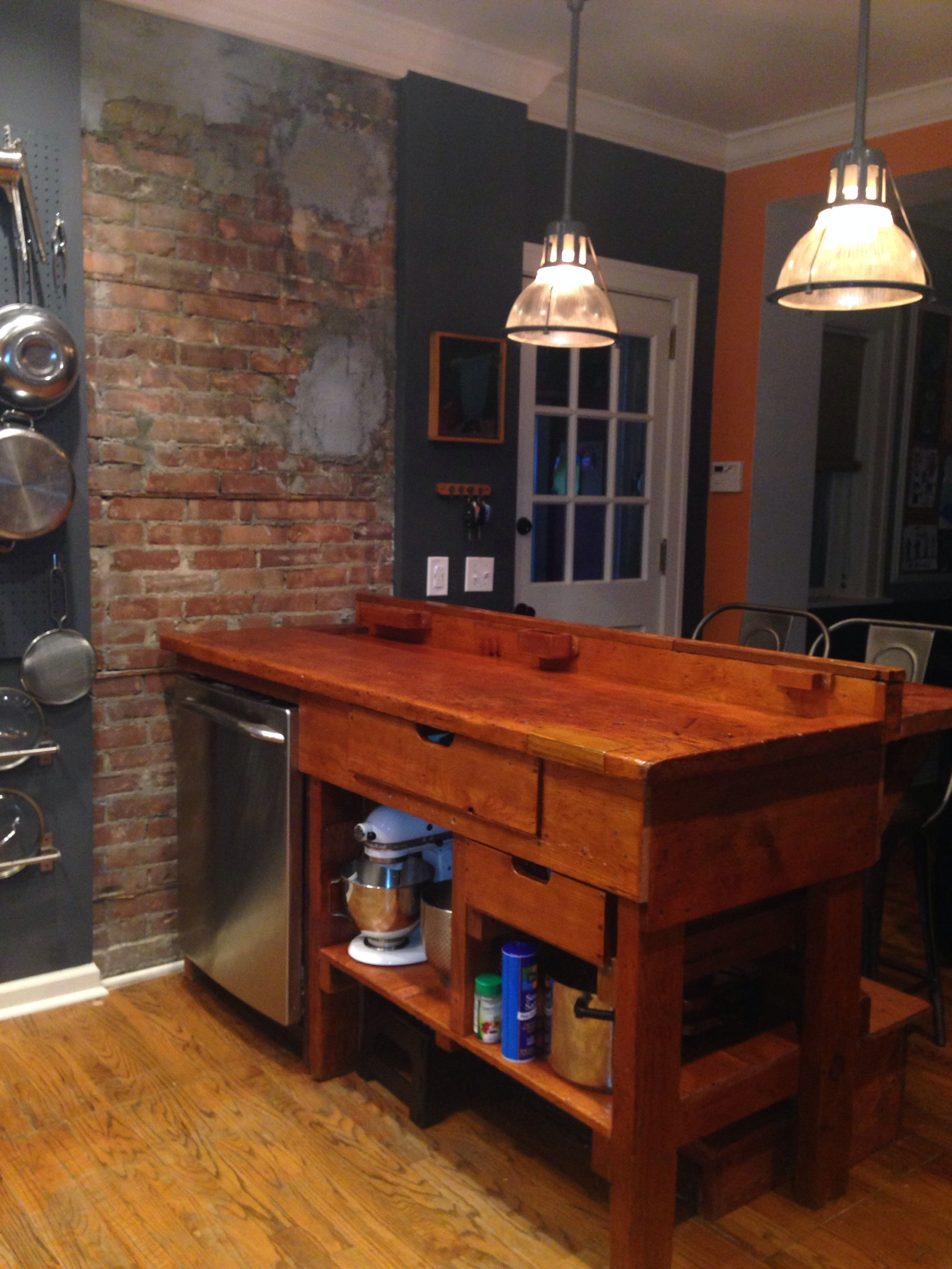 Antique workbench as kitchen island with exposed brick chimney