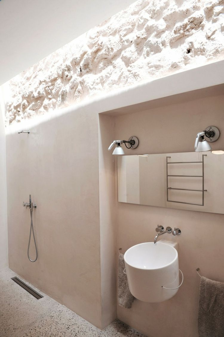 Mur en pierre apparente, mobilier en bois et plafond en poutres