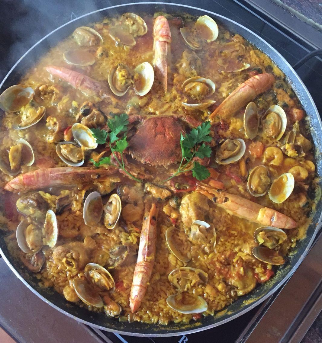 Paella de: pollo de corral, arroz, langostinos, gambas, mejillones, almejas y nécora.