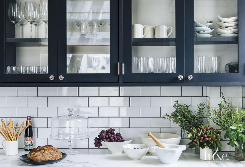 a modern black and white kitchen with subway tile backsplash