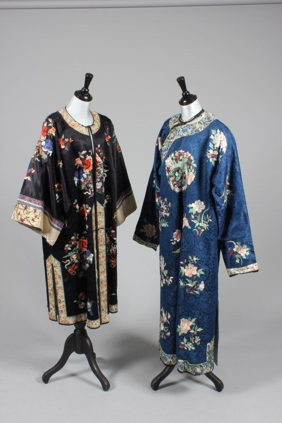 China, two ladies chang-fu, 1920s, one of royal blue damask worked with mythical bird roundels and spring blossom; the other of navy satin embroidered with peonies