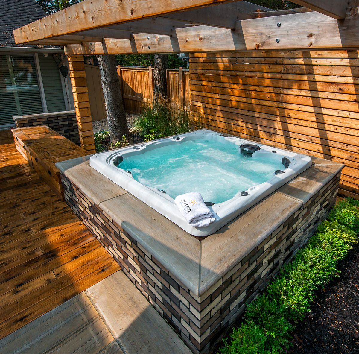 hight resolution of the wood and brick combination of this above ground hot tub install is beautifully done