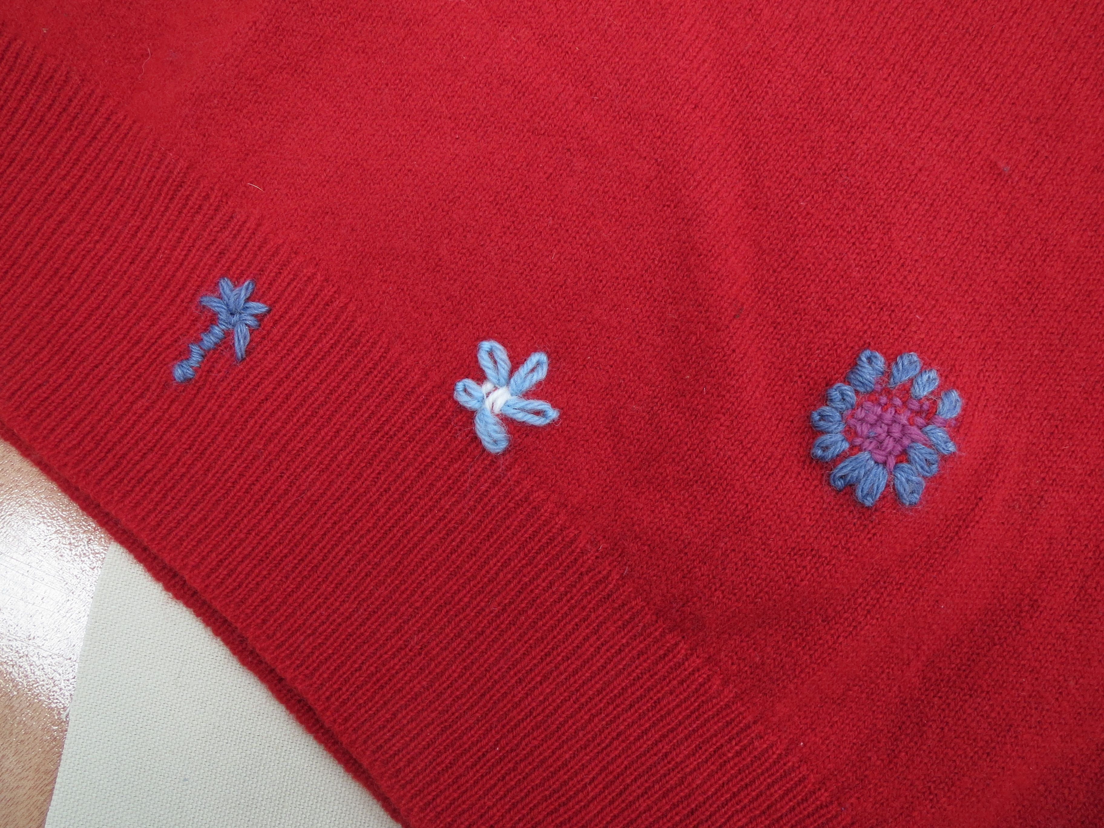 Moth holes repaired with floral embroidery stitches
