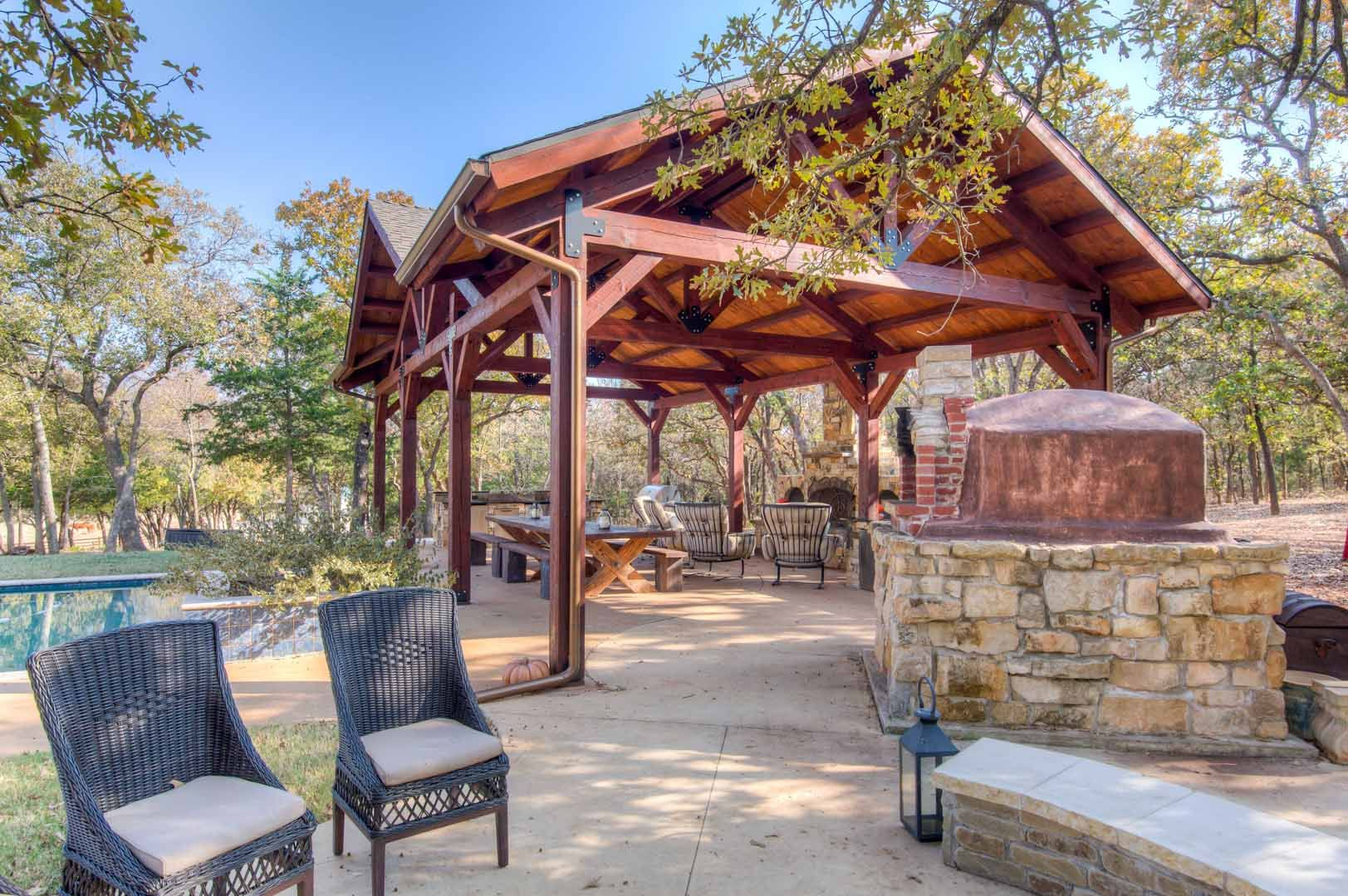 This Post And Beam Pavilion In Oklahoma Covers An Outdoor Kitchen And Sits Between A Pool And Outdoor Fireplace Pavilion Outdoor Outdoor Fireplace