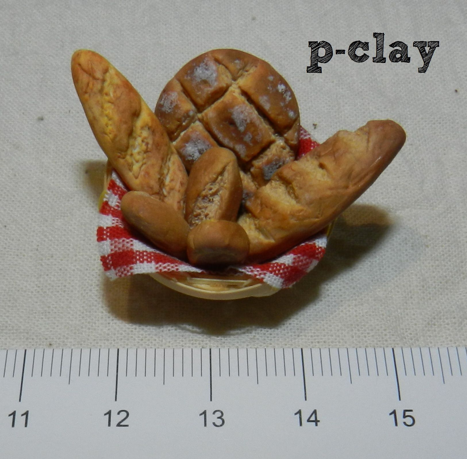 Basket of freshly baked bread (polymer clay miniature). Cesta de pan (arcilla polimérica, miniatura).